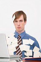 Businessman working on a laptop and covering with adhesive notes