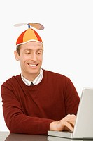 Businessman wearing a propeller beanie and working on a laptop