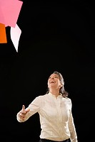 Businesswoman throwing papers in air