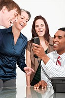 Businessman holding a telephone with three business executives smiling