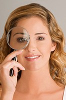 Close_up of a young woman looking through a magnifying glass