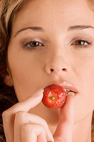 Portrait of a young woman eating a strawberry (thumbnail)
