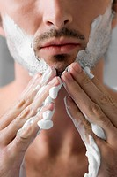 Close_up of a young man applying shaving cream on his face