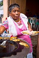 Portrait of a senior woman holding a plate of Mexican food, Cuetzalan, Puebla State, Mexico