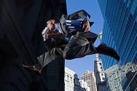 Low angle view of a businessman jumping in mid_air and drinking