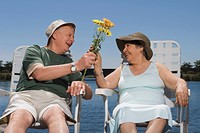 Senior man giving a bunch of flowers to a senior woman
