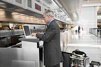 Side profile of a businessman using a laptop at an airport check_in counter