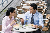 Businessman and a businesswoman having lunch at a sidewalk cafe
