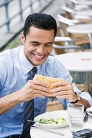 Close_up of a businessman eating a cheese sandwich and smiling