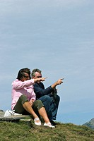 A man and a woman both 40 are sitting on a mountain summit and pointing with finger in one direction, the man holds a pair of binoculars in his hand, ...