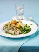 Salmon steak with pesto, potatoes and peas