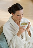Woman in bathrobe drinking tea