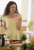 Woman smelling herbs and preparing meal
