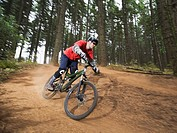 Mountain biker speeding down forest trail