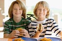 Boys eating hotdog and hamburger