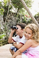 Boy looking through binoculars with girl