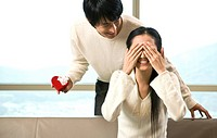 Young man giving a present to his wife covering eyes with her hands