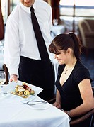 Waiter serving woman in restaurant