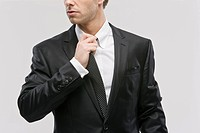 Businessman pulling at tie, close_up
