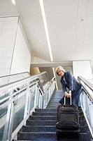 Businesswoman pulling suitcase up stairs