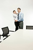 Business couple embracing in board room