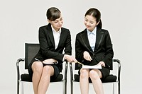 Two businesswomen sitting on chair