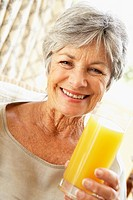 Senior Woman Smiling At Camera And Drinking Orange Juice