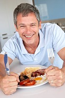 Middle Aged Man Eating Unhealthy Fried Breakfast