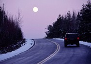 vehicle on a highway at twilight with the moon rising in the winter