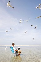 Man sitting in ocean surf with laptop