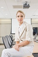 Portrait of businesswoman sitting on conference room table