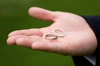 Two white gold wedding rings rest in a groom's open hand against a green background