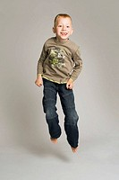 Blonde-haired, blue-eyed six year old boy in studio, jumping and smiling against a pale grey background. He wears jeans and a long-sleeved t-shirt