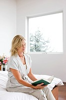 Woman reading book in bedroom