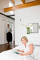 Man holding suit and woman reading book in bedroom