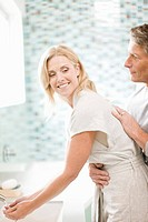 Man hugging woman washing hands in bathroom sink