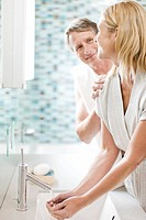 Man smiling at woman washing hands in bathroom sink