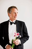 Portrait of man in tuxedo holding Oriental lily