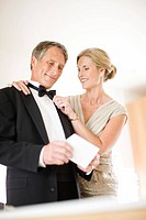 Couple in eveningwear holding wedding invitation
