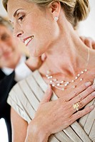 Man in tuxedo fastening necklace on woman