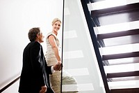 Couple in eveningwear ascending staircase