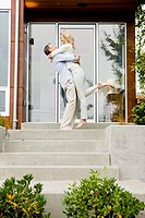 Man hugging and lifting woman on front stoop