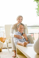 Portrait of couple hugging in living room (thumbnail)