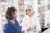 Pharmacist explaining prescription to customer