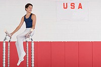 A gymnast sitting on parallel bars