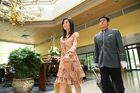 Young Woman And Bellhop Walking At Hotel Hall