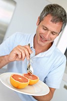 Middle Aged Man Eating Fresh Grapefruit