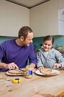 Father and daughter spreading peanut butter on bread