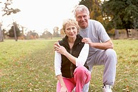 Portrait Of Senior Couple Crouching In The Park