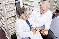 Pharmacists examining prescription bottle
